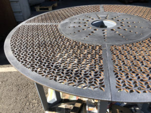 close up waterjet cut feature holes in corten steel fountain base