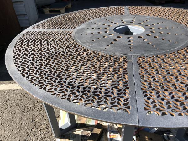 close up waterjet cut feature holes in corten steel fountain base